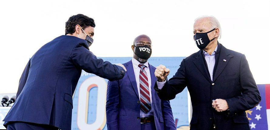 Jon Ossoff and Raphael Warnock Joe Biden bumping elbows